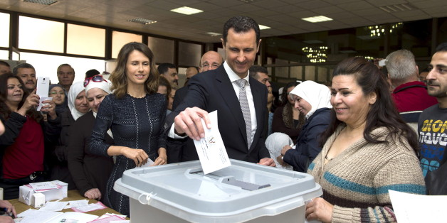 Syria's President Bashar al-Assad (C) casts his vote next to his wife Asma (centre left) inside a polling station during parliamentary elections in Damascus, Syria, in this handout picture provided by SANA on April 13, 2016. REUTERS/SANA/Handout via Reuters ATTENTION EDITORS - THIS PICTURE WAS PROVIDED BY A THIRD PARTY. REUTERS IS UNABLE TO INDEPENDENTLY VERIFY THE AUTHENTICITY, CONTENT, LOCATION OR DATE OF THIS IMAGE. FOR EDITORIAL USE ONLY. NOT FOR SALE FOR MARKETING OR ADVERTISING CAMPAIGNS.