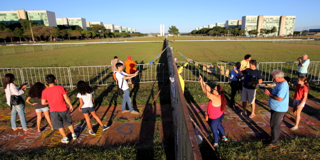 People take pictures of messages written on protective fences set up to separate demonstrators who are for and against the impeachment of President Dilma Rousseff in Brasilia, Brazil April 16, 2016. REUTERS/Paulo Whitaker