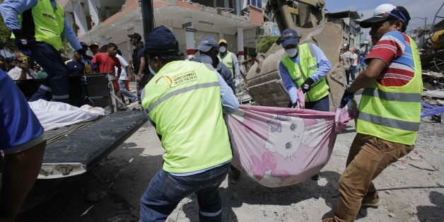 Volunteers carry a body pulled from the rubble in Pedernales, Ecuador, Sunday, April 17, 2016. Rescuers pulled survivors from rubble Sunday after the strongest earthquake to hit Ecuador in decades flattened buildings and buckled highways along its Pacific coast.  (AP Photo/Dolores Ochoa)