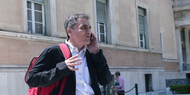 Greek Finance Minister Euclid Tsakalotos talks on his mobile phone outside the Greek parliament in Athens on July 22, 2015. Prime Minister Alexis Tsipras faced a new test of his authority in parliament on July 22, where MPs were to vote on a second batch of reforms to help unlock a bailout for Greece's stricken economy. The embattled premier last week faced a revolt by a fifth of the lawmakers in his radical-left Syriza party over changes to taxes, pensions and labour rules demanded by EU-IMF creditors.   AFP PHOTO / LOUISA GOULIAMAKI        (Photo credit should read LOUISA GOULIAMAKI/AFP/Getty Images)