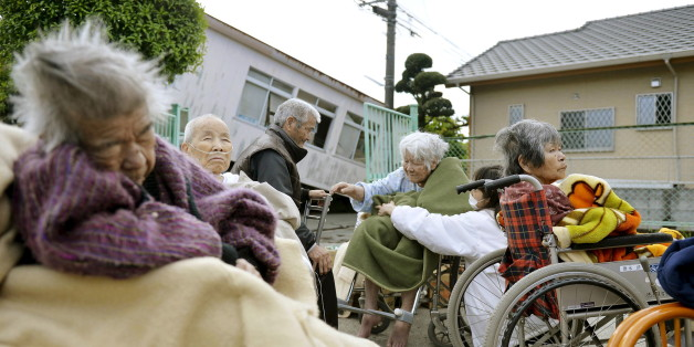 Evacuees from a nursing home wrap themselves in blankets as they take shelter outside their damaged nursing home caused by an earthquake in Mashiki town, Kumamoto prefecture, southern Japan, in this photo taken by Kyodo April 17, 2016. Mandatory credit REUTERS/Kyodo  ATTENTION EDITORS - FOR EDITORIAL USE ONLY. NOT FOR SALE FOR MARKETING OR ADVERTISING CAMPAIGNS. THIS IMAGE HAS BEEN SUPPLIED BY A THIRD PARTY. THIS PICTURE WAS PROCESSED BY REUTERS TO ENHANCE QUALITY. AN UNPROCESSED VERSION WILL BE