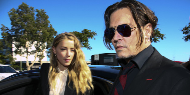 US actor Johnny Depp (R) and his wife Amber Heard arrive at a court in the Gold Coast on April 18, 2016. Depp and Heard arrived at an Australian court April 18 over Heard's alleged illegal importation of their two Yorkshire terrier dogs Boo and Pistol into the country in a private jet in 2015, as Depp was in Australia for the filming of the latest Pirates of the Carribean movie.    / AFP / Patrick HAMILTON        (Photo credit should read PATRICK HAMILTON/AFP/Getty Images)