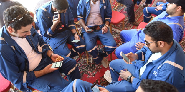 Kuwait Oil and Petrochemical Industries Union workers sit with their cellphones on the first day of an official strike over public sector pay reforms, in Ahmadi, Kuwait April 17, 2016. REUTERS/Stephanie McGehee
