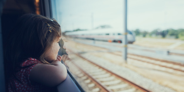 Young girl looking through the window in the train on the move