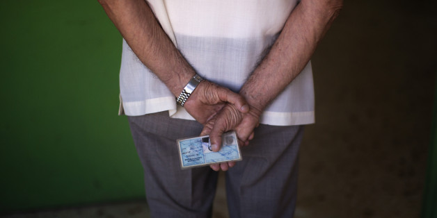 A man holds his ID card as he waits for his turn to cast his vote at a polling station in Athens, Sunday, July 5, 2015. Greeks were voting Sunday in a critical bailout referendum, with opinion polls showing people evenly split on whether to accept creditors' proposals for more austerity in exchange for rescue loans, or defiantly reject the deal. (AP Photo/Emilio Morenatti)