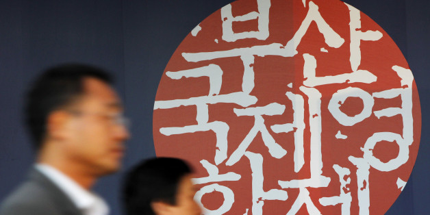 People walk past a logo of the 15th Pusan International Film Festival before the opening ceremony of the film festival in Busan, about 420 km (262 miles) southeast of Seoul, October 7, 2010.  REUTERS/Jo Yong-Hak (SOUTH KOREA - Tags: ENTERTAINMENT)
