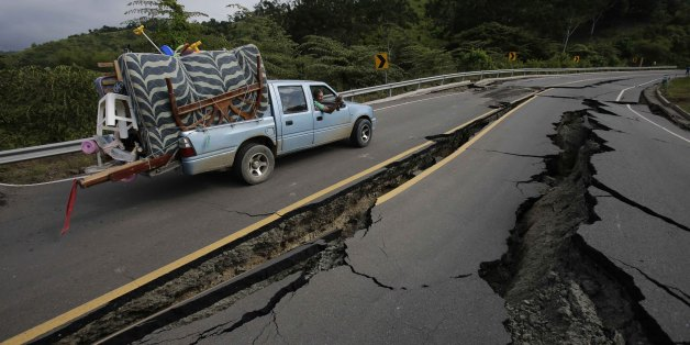 A truck moves the belongings of a family from Pedernales, over the earthquake destroyed road to Jama, in Ecuador, Monday, April 18, 2016. A Saturday night quake left a trail of ruin along Ecuador's Pacific Ocean coast. Hundreds have died, thousands are homeless and without electricity. (AP Photo/Dolores Ochoa)