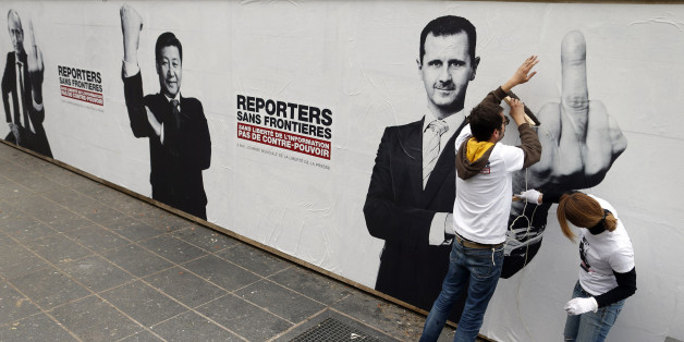 "Activists from Reporters Without Borders (RSF) paste a poster depicting Russia's President Vladimir Putin (L) and his counterparts from China, Xi Jinping (C) and Syria, Bashar al-Assad, on the Brancusi Atelier to mark the 20th annual World Press Freedom day in Paris May 3, 2013. The slogan reads, ""Without freedom of information, no counter-power"". REUTERS/Benoit Tessier (FRANCE - Tags: POLITICS CIVIL UNREST MEDIA) TEMPLATE OUT"
