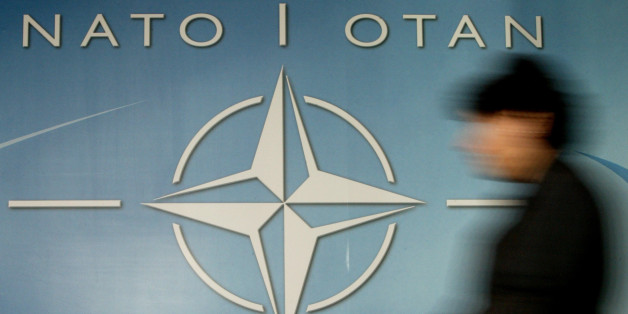 A woman walks past the NATO logo at the entrance of the Alliance