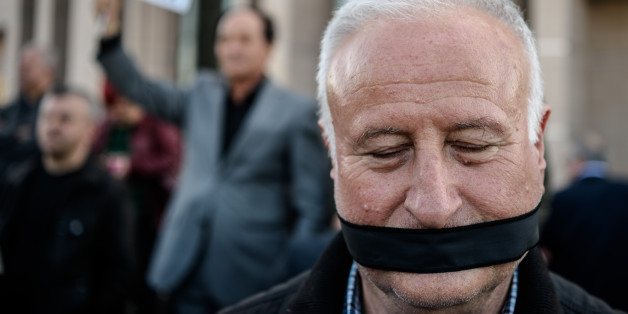 TOPSHOT - A demonstrator with his mouth covered, stands outside the Istanbul courthouse on April 1, 2016, where Turkish opposition Cumhuriyet daily's editor-in-chief Can Dundar and Ankara bureau chief Erdem Gul attend their trial. Cumhuriyet daily's editor-in-chief Can Dundar and Ankara bureau chief Erdem Gul face possible life terms on spying charges over a news report accusing President Recep Tayyip Erdogan's government of seeking to illicitly deliver arms bound for neighbouring Syria. / AFP / OZAN KOSE        (Photo credit should read OZAN KOSE/AFP/Getty Images)