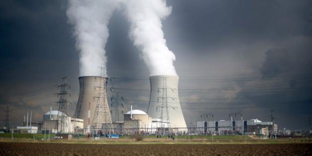 Dampf steigt hinter einer Windmühle bei Antwerpen (Belgien) aus den Kühltürmen des Atomkraftwerks Doel des Stromversorgers Electrabel, aufgenommen am 26.02.2016.