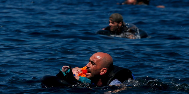 A Syrian refugee holding a baby swims towards the Greek island of Lesbos, September 12, 2015.  Alkis Konstantinidis: Another inflatable boat packed with dozens of migrants and refugees heading towards the shore. That's what I noticed in the distance. The sea was calm and they were cheering on the dinghy. Suddenly, some 200 metres away, the rear of the boat deflated for no obvious reason, and people started falling into the sea. Screams replaced cheers as they frantically tried to stay afloa