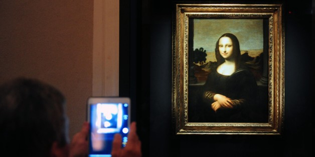Members of the media take pictures during the media preview of The World Premiere of Leonardo Da Vinci's painting 'Earlier Mona Lisa' exhibition in Singapore on December 15, 2014. The World Premiere of Leonardo Da Vinci's exhibition will begin on December 16 till February 1, 2015. AFP PHOTO / MOHD FYROL RESTRICTED TO EDITORIAL USE, MANDATORY MENTION OF THE ARTIST UPON PUBLICATION, TO ILLUSTRATE THE EVENT AS SPECIFIED IN THE CAPTION.        (Photo credit should read MOHD FYROL/AFP/Getty Images)