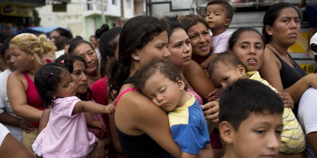 Women and children wait in a line for over an hour for free food and water from the government, days after an earthquake in Crucita, Ecuador, Thursday, April 21, 2016. The damage from the 7.8-magnitude quake adds to already heavy economic hardships being felt in this OPEC nation triggered by the collapse in world oil prices.  (AP Photo/Rodrigo Abd)