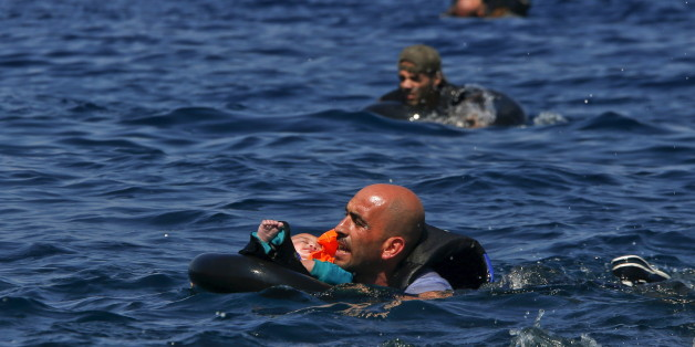 A Syrian refugee holding a baby in a life tube swims towards the shore after their dinghy deflated some 100m away before reaching the Greek island of Lesbos, September 13, 2015. Reuters and The New York Times shared the Pulitzer Prize for breaking news photography for images of the migrant crisis in Europe and the Middle East. REUTERS/Alkis Konstantinidis      TPX IMAGES OF THE DAY