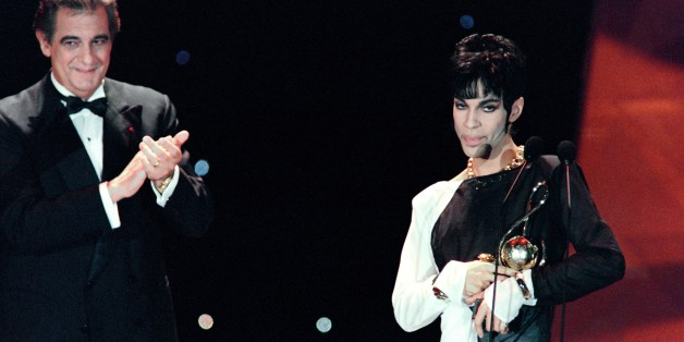 This photo taken on May 4, 1994 shows musician Prince (R) acknowledging applause after receiving from Italian tenor Placido Domingo (L) the 'Outstanding Contribution to the Pop Industry' award during the World Music Awards ceremony in Monaco.   Pop icon Prince -- whose pioneering brand of danceable funk made him one of music's most influential figures -- died on April 21, 2016 at his compound in Minnesota. He was 57. The announcement came just a week after the Grammy and Oscar winner was taken to hospital with a bad bout of influenza, although he made light of his health problems after the scare.   / AFP / Patrick HERTZOG        (Photo credit should read PATRICK HERTZOG/AFP/Getty Images)
