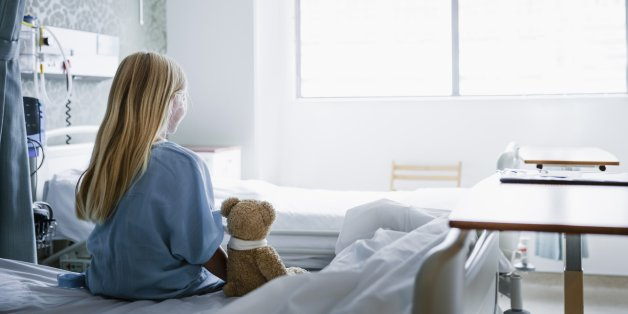 Little girl sitting on a hospital bed with her Teddy Bear by her side looking towards a window.