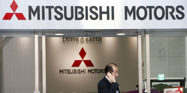 A man talking on the mobile phone walks out from the headquarters of Mitsubishi Motors Corp. in Tokyo Tuesday, Feb. 5, 2013. Mitsubishi Motors, which did not break down quarterly results, reported Tuesday that nine-month profit through December totaled 17.3 billion yen ($188 million), up 27 percent from the same period the previous fiscal year. (AP Photo/Koji Sasahara)