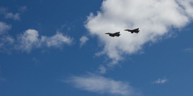 Two F-16s flying past at an airshow in Kristiansand, Norway. Beautifully contrasted in front of white clouds.