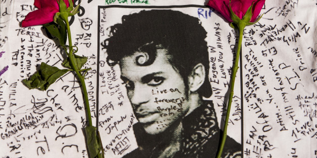Flowers lay on a T-shirt signed by fans of singer Prince at a makeshift memorial place created outside Apollo Theater in New York, Friday, April 22, 2016. The pop star died Thursday at the age of 57. (AP Photo/Andres Kudacki)
