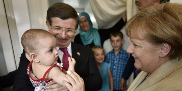 GAZIANTEP, TURKEY - APRIL 23:  In this photo provided by the German Government Press Office (BPA), Turkey's Prime Minister, Ahmet Davutoglu holds a child as German Chancellor Angela Merkel speaks to her in a refugee camp on April 23, 2016 in Gaziantep, Turkey. Merkel is in Germany to commence the EU aid program for Syrians in Turkey and visit a refugee camp.  (Photo by Steffen Kugler - Pool/Bundesregierung via Getty Images)