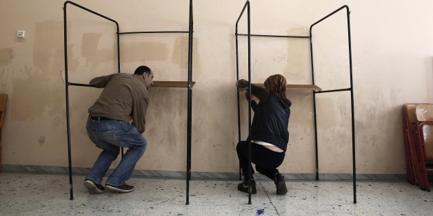 Municipal workers assemble voting booths at a voting center in Athens, Friday, Jan. 23, 2015. Prime Minister Antonis Samaras' New Democracy party has failed so far to overcome a gap in opinion polls with the anti-bailout Syriza party ahead of the Jan. 25 general election. (AP Photo/Petros Giannakouris)