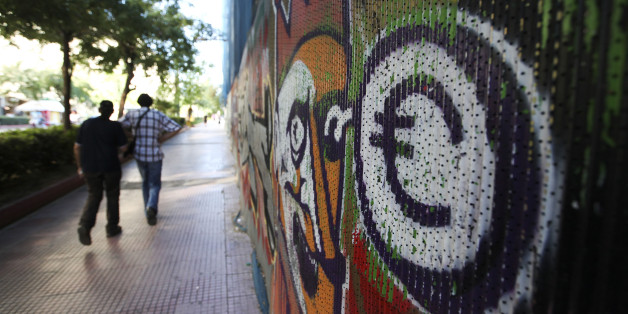 Pedestrians pass a graffiti artwork showing a euro symbol on a street in Athens, Greece, on Thursday, June 21, 2012. Lenders of 240 billion euros ($301 billion) to Greece offered no sign of granting extra time for the newly installed Athens government to meet deficit-cut targets. Photographer: Chris Ratcliffe/Bloomberg via Getty Images