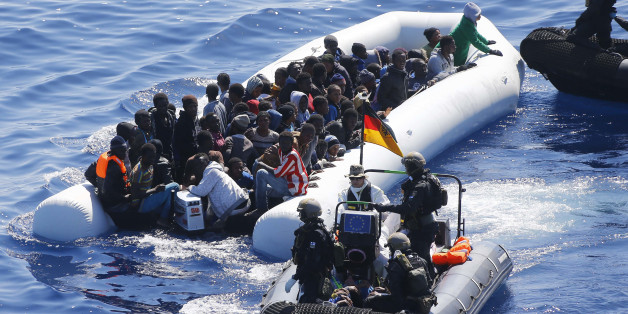 In this March 29, 2016 picture German Navy sailors ad Finish Special Forces surround a boat with  migrants near the German combat supply ship 'Frankfurt am Main' during   EUNAVFOR MED Operation Sophia in the Mediterranean Sea off the coast of Libya .  (AP Photo/Matthias Schrader)