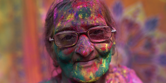 A widow daubed in colours takes part in Holi celebrations organised by non-governmental organisation Sulabh International at a widows' ashram at Vrindavan, in the northern Indian state of Uttar Pradesh March 3, 2015. Traditionally in Hindu culture, widows are expected to renounce earthly pleasure so they do not celebrate Holi. But women at the shelter for widows, who have been abandoned by their families, celebrated the festival by throwing flowers and coloured powder. Holi, also known as the Festival of Colours, heralds the beginning of spring and is celebrated all over India. REUTERS/Ahmad Masood (INDIA - Tags: RELIGION SOCIETY ANNIVERSARY)