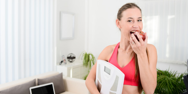 cheerful young woman holding scales and eating fruit weight loss program