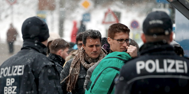 Migrants stand in queue during heavy snowfall before passing Austrian-German border in Wegscheid in Austria, near Passau November 22, 2015. REUTERS/Michael Dalder