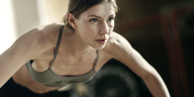 Close-up of focused female boxer doing push-ups in the gym