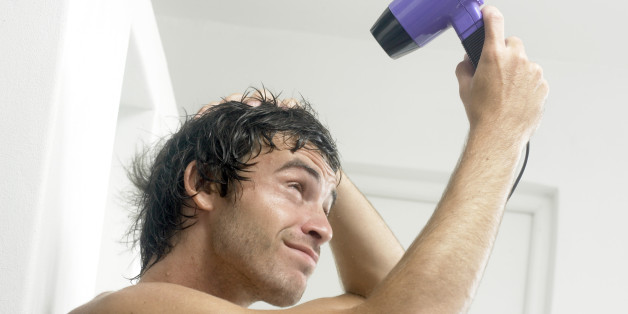 Man blow drying hair