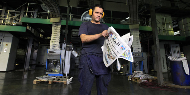 A pressman checks newly printed Al Khabar newspapers for printing errors at the printing presses owned by Algeria's Al Khabar and El Watan newspapers in Algiers September 20, 2010.  REUTERS/Zohra Bensemra (ALGERIA  - Tags:  MEDIA)