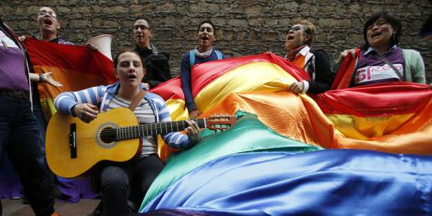 Activists sing as they wait outside a local court where Carlos Hernando and Gonzalo Ruiz were the first same-sex couple in Colombia to be joined in a civil union, in Bogota, Colombia, Wednesday, July 24, 2013. (AP Photo/Fernando Vergara)