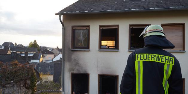 Archivbild: in Feuerwehrmann steht am 27.04.2016 in Frücht (Rheinland-Pfalz) vor einem vom Rauch geschwärzten Wohnhaus. Bei einem Brand ist dort ein Hausbewohner ums Leben gekommen.