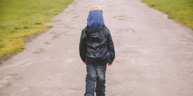 Little boy walking down a country road in the Lake District on a rainy day