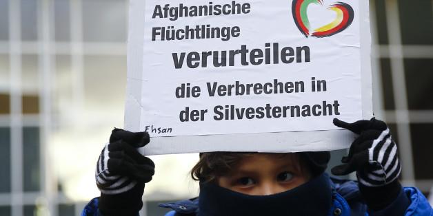Ein afganisches Flüchtlingskind hält nach der Kölner Silvesternacht ein Plakat hoch, dass die Übergriffe verurteilt