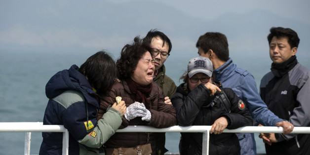 Relatives of victims of the sinking of the ferry Sewol weep as they stand on the deck of a boat during a visit to the site where the ferry sank off the coast of South Korea's southern island of Jindo Wednesday, April 15, 2015. A solemn crowd of relatives of some of the 304 people _ mostly school kids _ who died in a ferry sinking gathered at a small South Korean port Wednesday, a day before the first anniversary of one of the country's deadliest sea disasters. (Ed Jones/Pool Photo via AP)