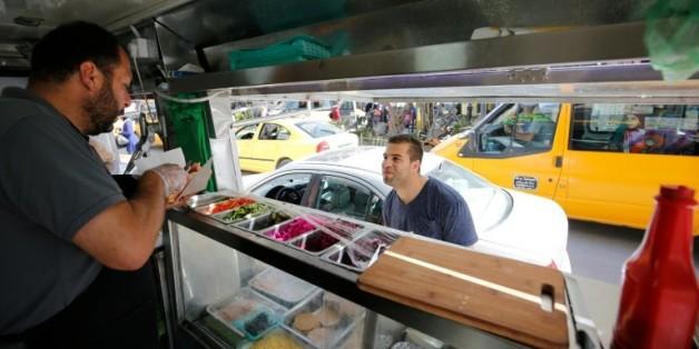 """Khaldoun al-Barghouthi, co-propriétaire du food-truck """"Food Train"""" sert un client à Ramallah, dans les Territoires palestiniens, le 3 mai 2016"""