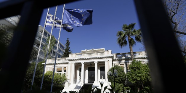 The Greek and the European Union flags are wave outside Maximos Mansion, office of the Prime Minister during a ministerial meeting in Athens, Wednesday, May 13, 2015. Greece's prime minister Alexis Tsipras was holding his second ministerial meeting in as many days Wednesday, when official data confirmed the cash-strapped country is back in recession amid concern over much-delayed bailout talks with creditors. (AP Photo/Thanassis Stavrakis)