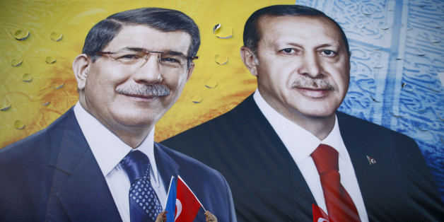 Supporters of the ruling AK Party hold national and party flags as they stand in front of a banner showing Turkish President Tayyip Erdogan and Prime Minister Ahmet Davutoglu (L) together during an election rally in the central Anatolian city of Konya, Turkey, October 30, 2015. REUTERS/Umit Bektas/File Photo