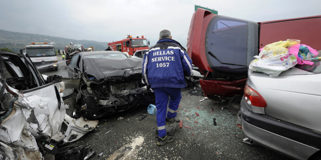 A worker from a road assistance company walks through destroyed cars following a massive car accident on a motorway in northern Greece October 5, 2014. Greek media reported that a truck caused a pile-up with dozens of cars in which four people were killed and at least 20 were injured on Egnatia motorway a few kilometres off Thessaloniki.    REUTERS/Alexandros Avramidis (GREECE - Tags: SOCIETY DISASTER TRANSPORT TPX IMAGES OF THE DAY)
