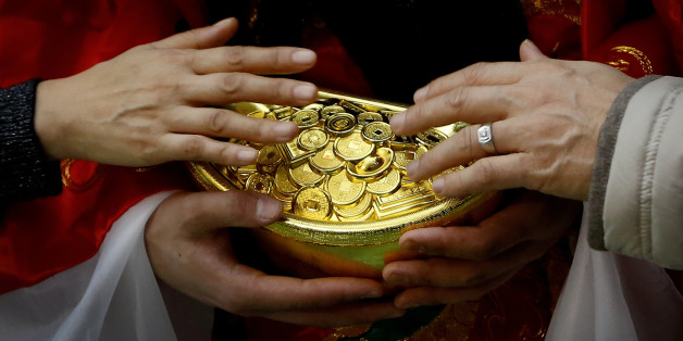 A man  and a woman touch gold coins which are carried by a worker dressed as a God of Fortune at a shopping mall in Beijing, Friday, Feb. 12, 2016. Millions of Chinese are celebrating the Lunar New Year, which marks the Year of the Monkey on the Chinese zodiac. (AP Photo/Andy Wong)