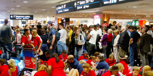 Hundreds of people wait outside the customs check point at Sydney international airport, Wednesday, July 7, 2004, after all fights were delayed due to a security breech. Delays of more than an hour were caused by a man being stopped while trying to get onto a flight without a boarding pass. (AP Photo/Rob Griffith)
