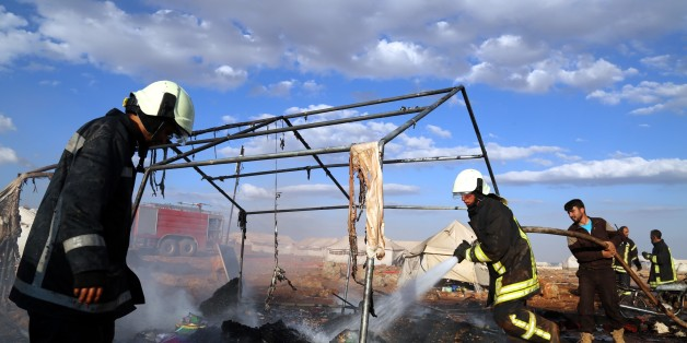 IDLIB, SYRIA - MAY 05: Firefighters extinguish fire after a Syrian regime warcraft targeted the Kamuna refugee camp near the Sarmada town of Idlib province, Syria on May 05, 2016. Eight people were killed and another 30 injured when a regime warcraft targeted the Kamuna refugee camp. (Photo by Abdulfetah Huseyin/Anadolu Agency/Getty Images)