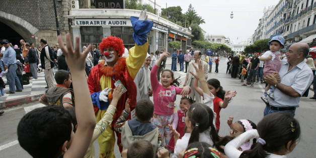 """A clown performs with children at the main street of Didouch Mourad on """"A day without cars"""" in Algiers May 16, 2008. This is the first time local municipality authorities called for """"A day without cars"""" in the capital's center to raise awareness on environmental protection. REUTERS/Louafi Larbi (ALGERIA)"""