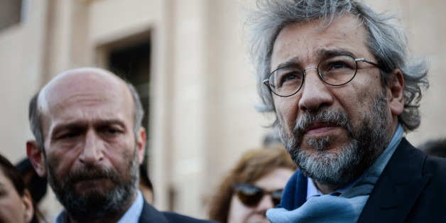 Turkish opposition Cumhuriyet daily's editor-in-chief Can Dundar (R) and Ankara bureau chief Erdem Gul (L) speak to media as they arrive at the Istanbul courthouse for their trial on April 1, 2016.  Cumhuriyet daily's editor-in-chief Can Dundar and Ankara bureau chief Erdem Gul face possible life terms on spying charges over a news report accusing President Recep Tayyip Erdogan's government of seeking to illicitly deliver arms bound for neighbouring Syria. / AFP / OZAN KOSE        (Photo credit should read OZAN KOSE/AFP/Getty Images)
