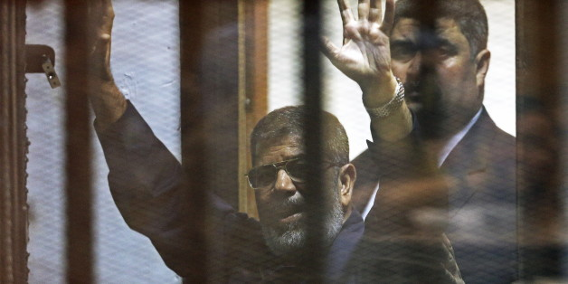 Deposed Egyptian President Mohamed Mursi greets his lawyers and people from behind bars after his verdict at a court on the outskirts of Cairo, Egypt June 16, 2015. An Egyptian court sentenced deposed President Mohamed Mursi to death on Tuesday on charges of killing, kidnapping and other offences during a 2011 mass jail break.The general guide of the Muslim Brotherhood, Mohamed Badie, and four other Brotherhood leaders were also handed the death penalty. More than 80 others were sentenced to dea