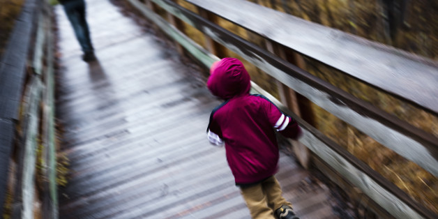 Little boy running after his mother on footbridge, blurred motion. Rock Creek, Montana.
